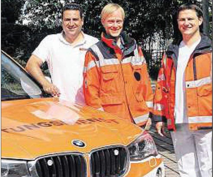 Sharam Tabrizi (l.) mit zweien seiner Kollegen, Alexander Pfäffle und Christian Niemann, vor ihrem Einsatzfahrzeug, das vom BRK gestellt wird. Foto: Budke